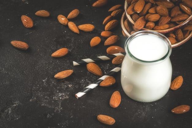 Roślinne źródła białka. wegańskie zdrowe jedzenie. mała butelka porcji mleka migdałowego. na tle migdałów orzechowych na czarnym betonowym stole. selektywne ustawianie ostrości.