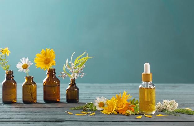 Rośliny lecznicze i brązowe butelki na niebieskiej powierzchni