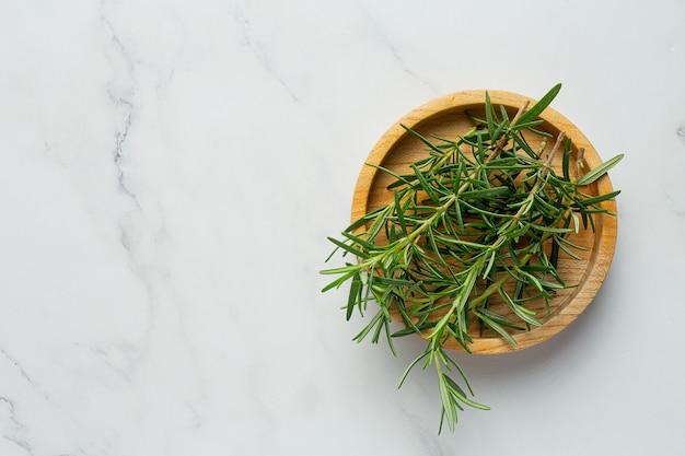 Rośliny rozmarynu układa się na podłodze z białego marmuru