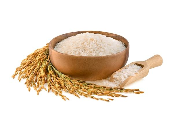 Rośliny ryżowe, ziarna tajskiego ryżu jaśminowego w drewnianej misce na białej powierzchni
