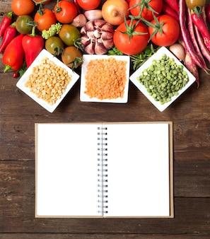 Rośliny strączkowe w miskach i warzywach na drewnianym blacie widok z notebookiem