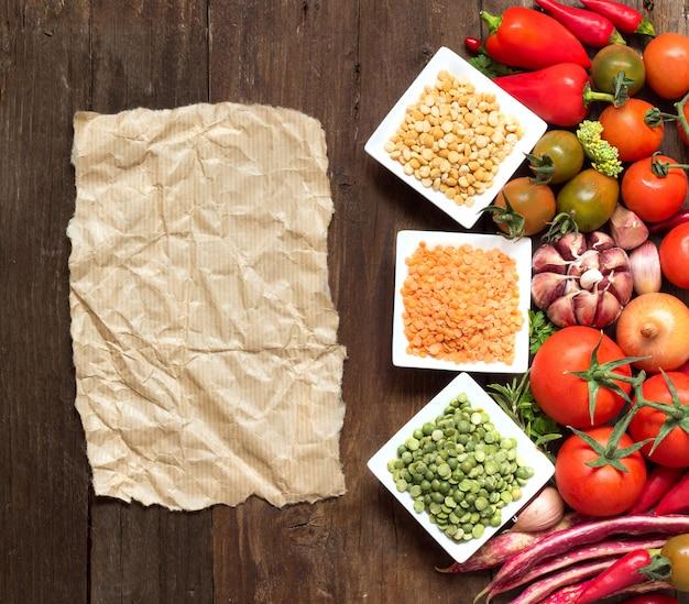 Rośliny strączkowe w miskach i warzywach na drewnianym blacie widok z papierem