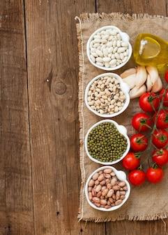 Rośliny strączkowe w miskach, pomidorach, czosnku i oliwie z oliwek na drewnianym stole widok z góry z miejsca kopiowania