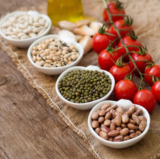 Rośliny strączkowe w miskach, pomidorach, czosnku i oliwie z oliwek na drewnianym stole z bliska