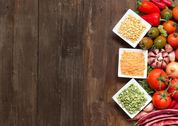 Rośliny strączkowe w pucharach i warzywach na drewnianym stołowym odgórnym widoku z kopii przestrzenią