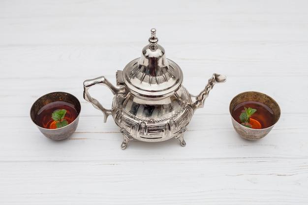 Rośliny w filiżankach herbaty w pobliżu rocznika czajniczek