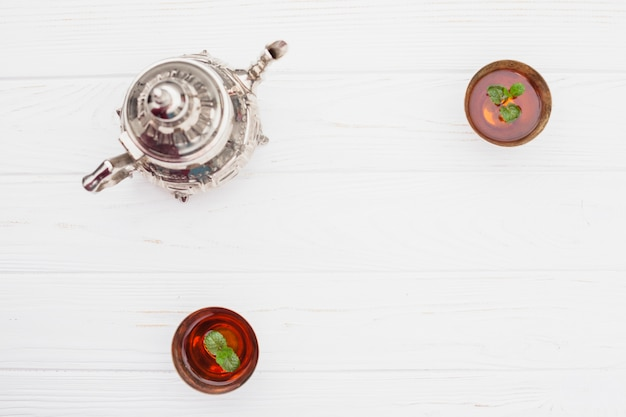 Rośliny w filiżankach herbaty w pobliżu rocznika czajnika