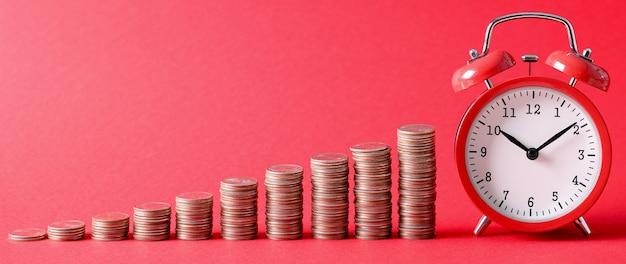 Rosnące stosy monet wyrównane z czerwonym budzikiem na dziesięć rano na czerwonym tle. rodzaje koncepcji lokat bankowych