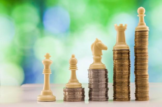 Rosnące stosy monet z figurami szachowymi stojącymi na monetach oznaczają siłę i rozwój kariery. wzrost finansowy, oszczędzanie pieniędzy, bogactwo finansów biznesowych i sukces koncepcji.