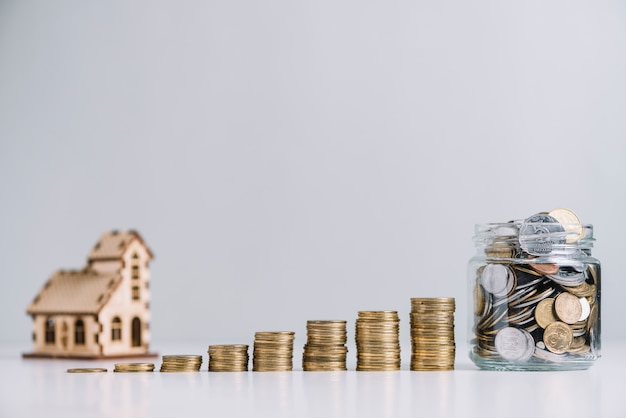 Rosnące ułożone monety i szklany słoik przed modelem domu