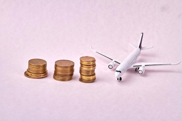 Rosnący stos monet i zabawkowy model samolotu