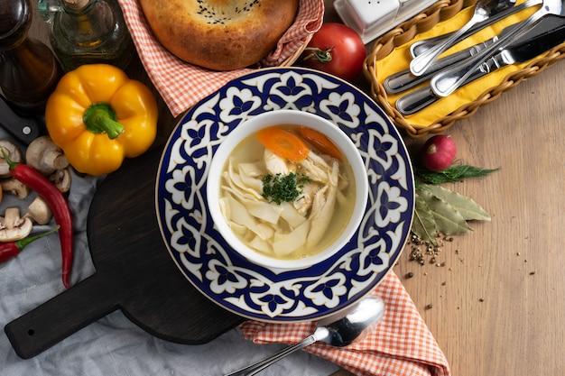 Rosół drobiowy z makaronem, marchewką i koperkiem na talerzu z tradycyjnym uzbeckim