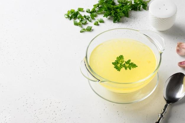 Rosół drobiowy z zieleniną, czosnkiem, cebulą w szklanej misce.