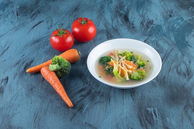 Rosół z brokułami i marchewką w misce obok warzyw na niebieskiej powierzchni.