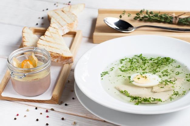 Rosół z jajkiem i foie gras na stole.