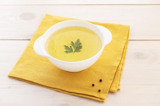 Rosół z kości z pietruszką w misce na żółtej serwetce