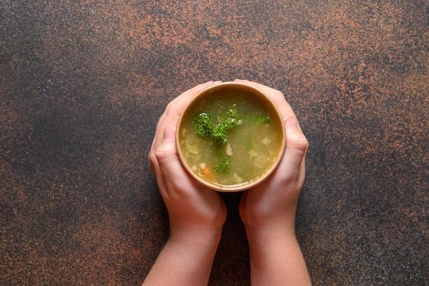 Rosół z kurczaka z zielenią w papierowych pojemnikach rzemieślniczych w dłoni dziecka