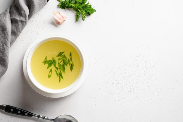 Rosół z kurczaka z zieloną cebulą w białej misce na białym stole. skopiuj miejsce widok z góry.