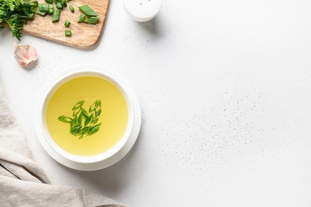 Rosół z kurczaka z zieloną cebulą w białej misce na białym tle.