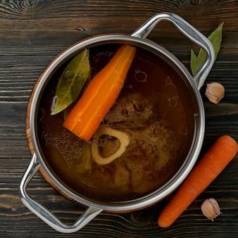 Rosół z wołowiny, ossobuco na kości, bogata zupa w rondlu, długie powolne, marne gotowanie.