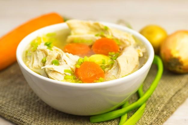 Rosół zupa z kurczaka i warzywa w białej misce na starej rustykalnej drewnianej desce do krojenia. ścieśniać. selektywna ostrość. skopiuj miejsce