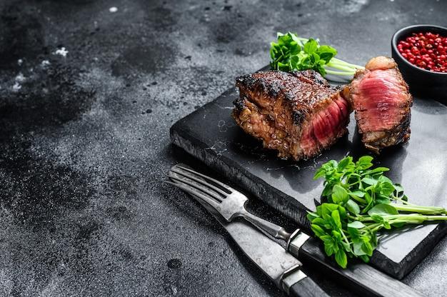 Rostbef z grilla lub stek nowojorski. czarne tło. widok z góry.