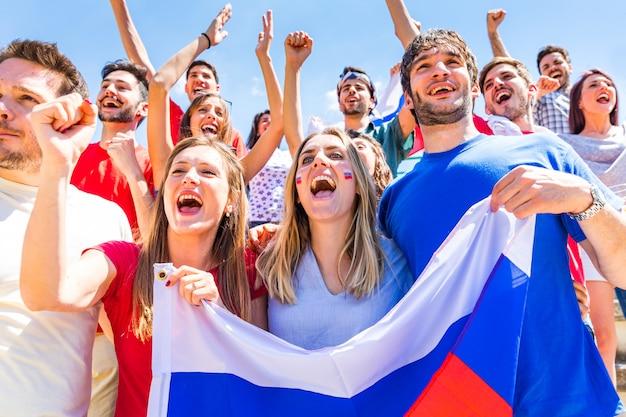 Rosyjscy kibice świętujący na stadionie z flagami