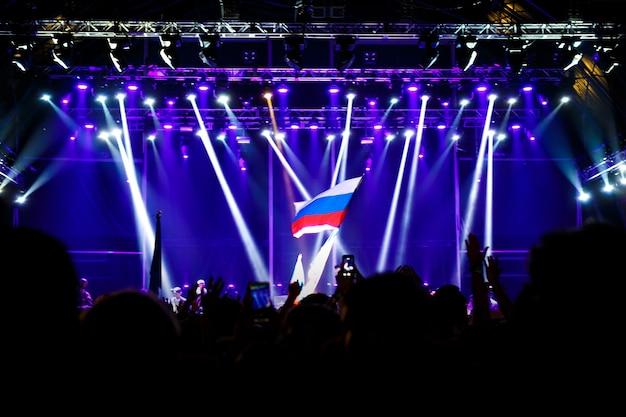 Rosyjska flaga na koncercie naprzeciw światła ze sceny