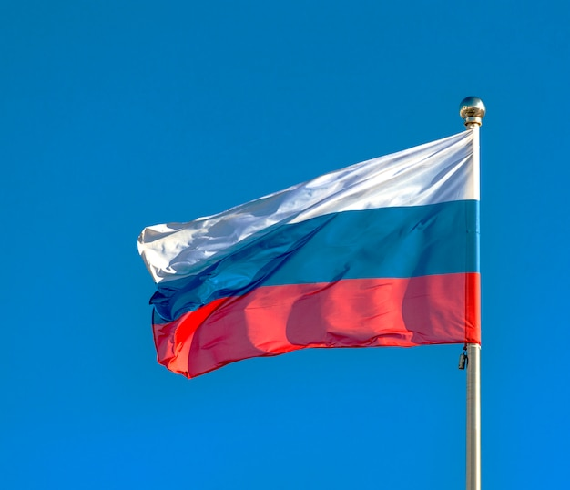 Rosyjska flaga na niebieskim niebie.