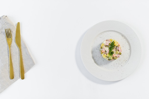 Rosyjska sałatka na białym talerzu z złotym nożem i rozwidleniem