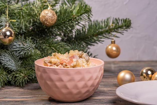 Rosyjska sałatka w różowej misce rosyjska sałatka w różowej misce na ozdobionej choince. olivier. narodowe rosyjskie danie noworoczne.