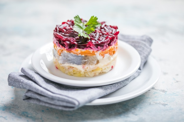 Rosyjska sałatka warstwowa z burakiem, ziemniakami, marchewką, marynowanym śledziem i majonezem