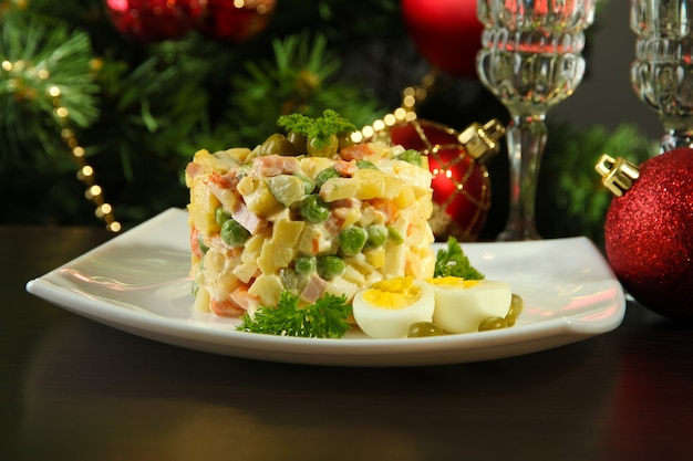 Rosyjska tradycyjna sałatka olivier, na drewnianym stole,
