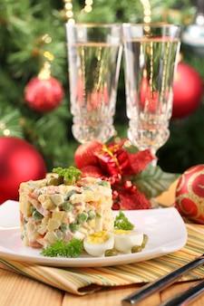 Rosyjska tradycyjna sałatka olivier, na kolorowej serwetce, na drewnianym stole, na jasnym tle