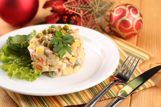 Rosyjska tradycyjna sałatka olivier, na kolorowej serwetce, na drewnianym stole,