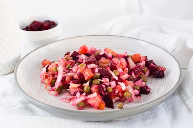 Rosyjska tradycyjna sałatka z warzywami - winegret na talerzu i miska buraków na stole na szmatce. zbliżenie