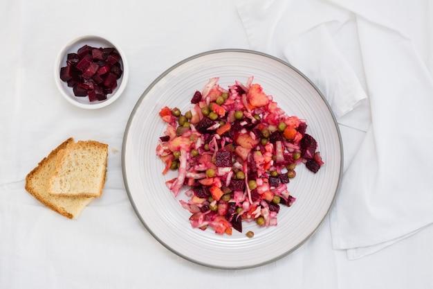 Rosyjska tradycyjna sałatka z warzywami - winegret na talerzu, pieczywo i miska buraków na stole na szmatce. widok z góry