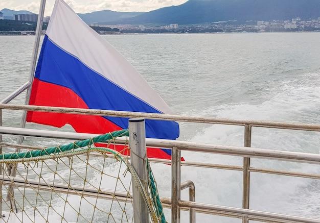 Rosyjska trójkolorowa flaga na statku, na tle morza i wybrzeża z nadmorskim miastem, świtem, latem.