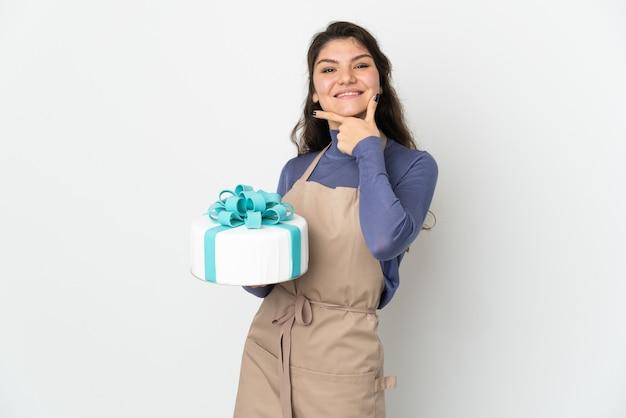 Rosyjski cukiernik trzyma duży tort na białej ścianie szczęśliwy i uśmiechnięty