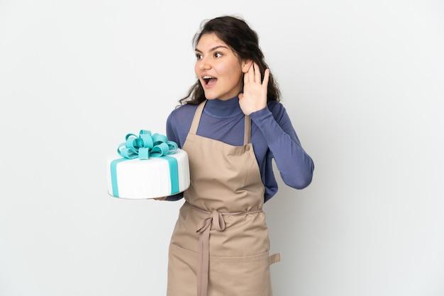 Rosyjski cukiernik, trzymając duży tort na białym tle na białej ścianie, słuchając czegoś, kładąc rękę na uchu