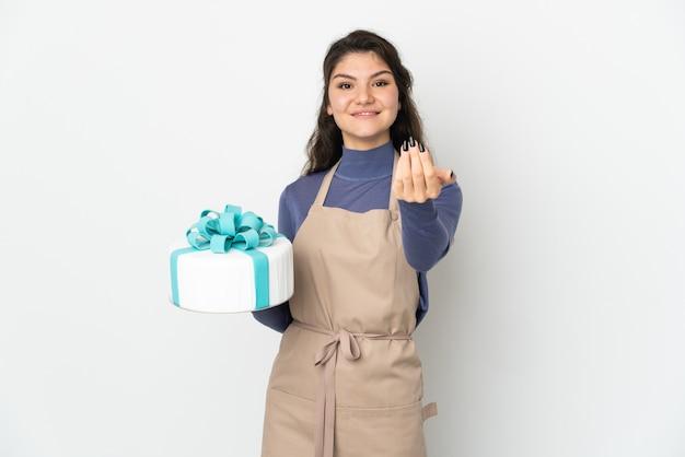 Rosyjski cukiernik, trzymając duży tort na białym tle na białej ścianie, zachęcając do przyjścia z ręką. cieszę się, że przyszedłeś