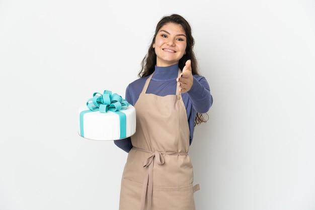 Rosyjski cukiernik trzymający duży tort na białym tle, ściskając ręce, aby zamknąć dobrą ofertę