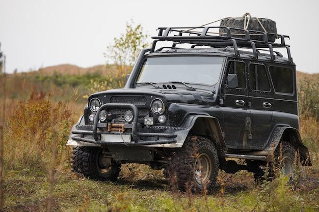 Rosyjski czarny brutalny samochód terenowy uaz na łące