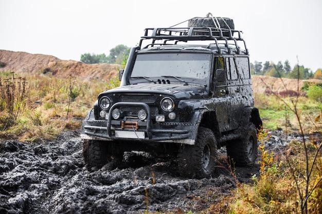 Rosyjski czarny brutalny samochód terenowy uaz w błocie