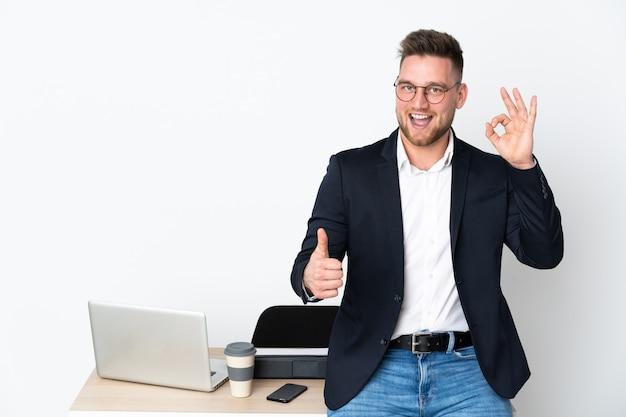 Rosyjski mężczyzna w biurze na białej ścianie pokazuje ok znaka i kciuka up gestykuluje
