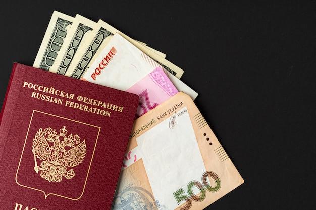 Rosyjski paszport z pieniędzmi w środku. dolary amerykańskie, ruble rosyjskie i hrywna ukraińska