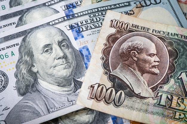 Rosyjski rubel sowiecki i 100 dolarów amerykańskich. konfrontacja systemu kapitalistycznego i socjalistycznego. zimna wojna. portrety włodzimierza lenina i benjamina franklina w walucie krajowej.