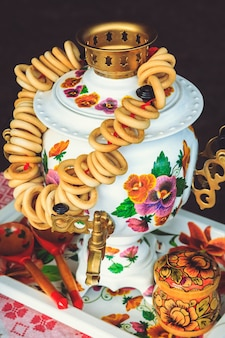 Rosyjski samowar z bajgielami na herbatę na tacy z łyżeczkami