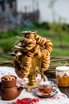 Rosyjski samowar z herbatą i pączkami na drewnianym stole