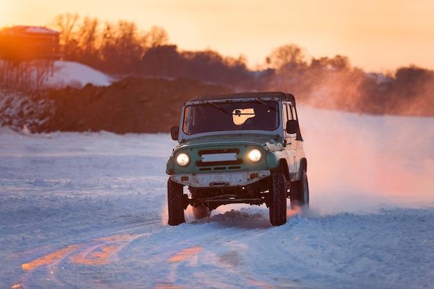 Rosyjski uaz 469 poruszający się po lodzie rzeki frosn o zachodzie słońca